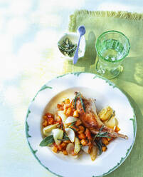 Overhead view of leg of rabbit with onions and vegetables on table outdoors - PPXF00201
