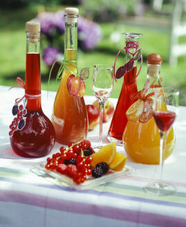 Homemade fruit liqueur in a carafe on the table in the garden. Peach liqueur, blackberry liqueur, currant liqueur, raspberry liqueur and orange liqueur. - PPXF00204