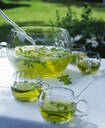Close up of woodruff punch in glass container ontable outside in garden - PPXF00216