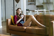 Relaxed young woman eating cereals in living room at home - GIOF06664