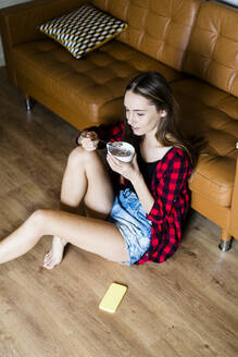 Relaxed young woman eating cereals in living room at home - GIOF06667