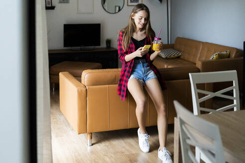 Happy young woman with cell phone and healthy drink at home - GIOF06685