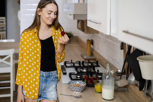 Young woman having breakfast in kitchen at home - GIOF06697