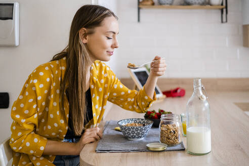 Young woman enjoying breakfast in kitchen at home - GIOF06700
