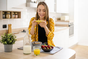 Happy young woman using cell phone and having breakfast in kitchen at home - GIOF06706