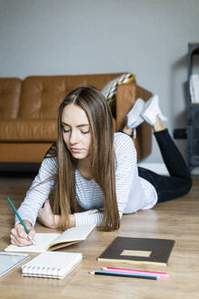 Young woman lying on the floor at home taking notes - GIOF06712