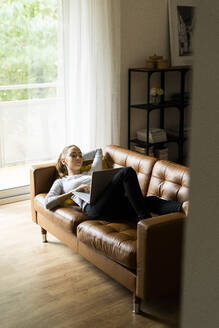 Young woman lying on couch at home using laptop - GIOF06721