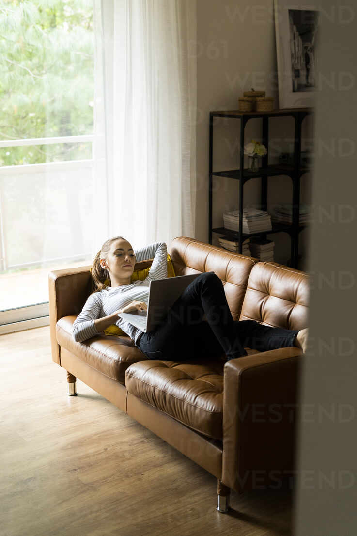 Young woman lying on couch at home using laptop - GIOF06721 - Giorgio Fochesato/Westend61