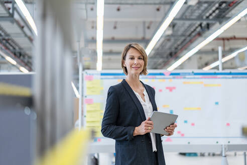 Portrait of confident businesswoman with tablet in a factory hall - DIGF07279