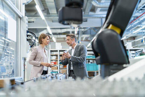 Businessman and businesswoman talking in a modern factory hall - DIGF07312