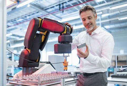 Confident businessman holding workpiece in a modern factory hall - DIGF07330