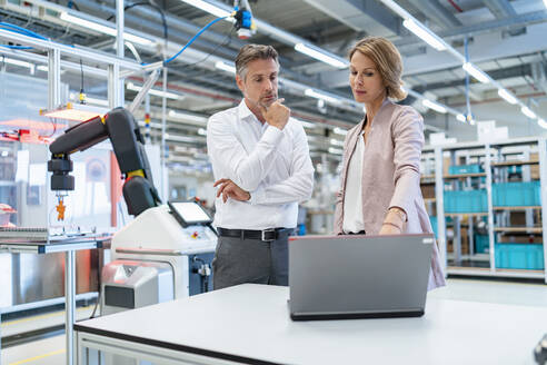 Businessman and businesswoman with laptop talking in a modern factory hall - DIGF07342