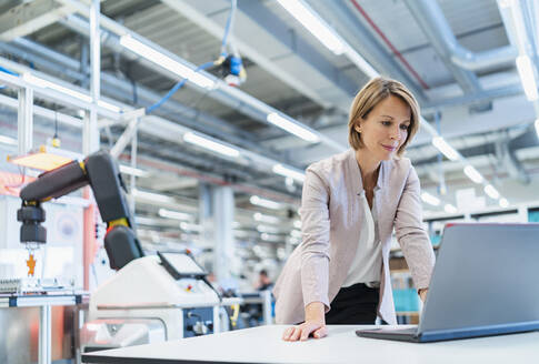 Businesswoman in a modern factory hall using laptop - DIGF07345