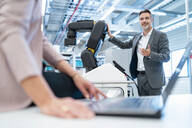 Businessman and businesswoman with laptop and robot in a modern factory hall - DIGF07351