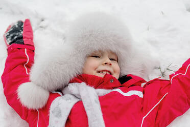 Smiling girl lying in the snow - OGF00017