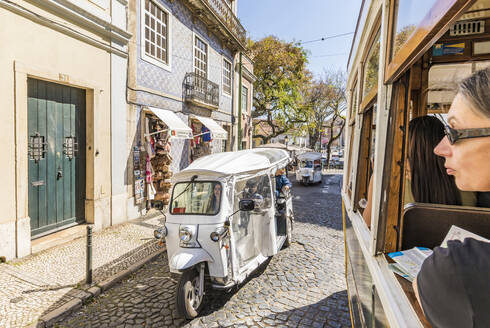 Portugal, Lisbon, Tram and tuk tuk on street in old town - WD05316