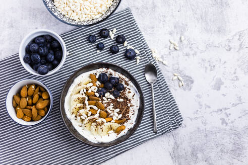 Bowl of fresh muesli, blueberries and almonds seen from above - GIOF06732