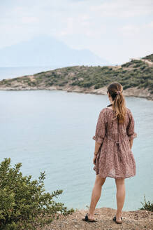 Young woman with summer dress looking at mount Athos, Greece. - BZF00493