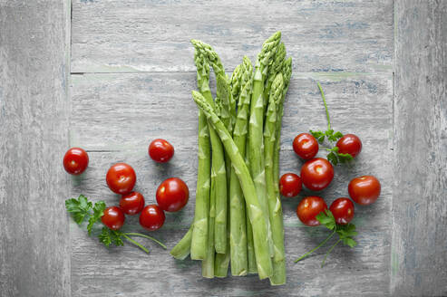 Green asparagus and cherry tomatoes on wooden table seen from above - ASF06456