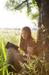 Portrait of smiling girl with book leaning against tree trunk on a meadow - LVF08162