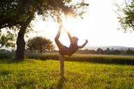Teenage girl performing yoga in grassy field at sunset - LVF08166