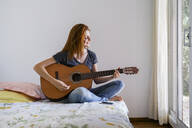 Young woman at home chilling in bedroom and playing guitar - AFVF03591