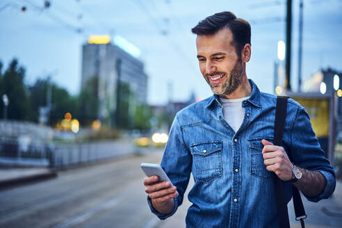 Man standing with smartphone waiting for evening commute after work - BSZF01084