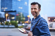 Portrait of smiling man standing in the city during evening and using smartphone - BSZF01087