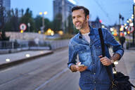 Smiling man with wireless headphones and smartphone waiting at tram stop during evening commute after work - BSZF01090