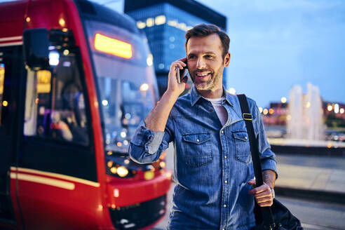Man making phone call on smartphone with tram in the background - BSZF01093