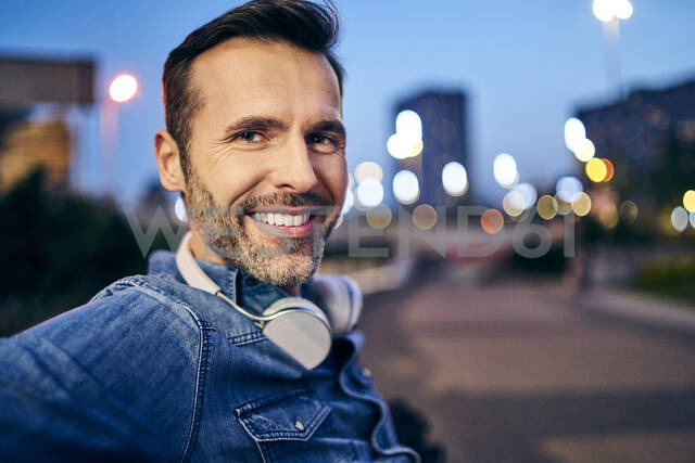 Portrait of a smiling man with headphones in the city in the evening - BSZF01099 - Bartek Szewczyk/Westend61