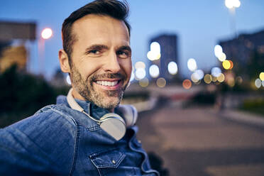 Portrait of a smiling man with headphones in the city in the evening - BSZF01099