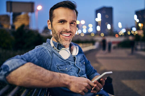 Portrait of a smiling man using his smartphone while sitting on a bench in the evening - BSZF01102