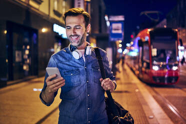 Smiling man using his smartphone in the city at night - BSZF01105