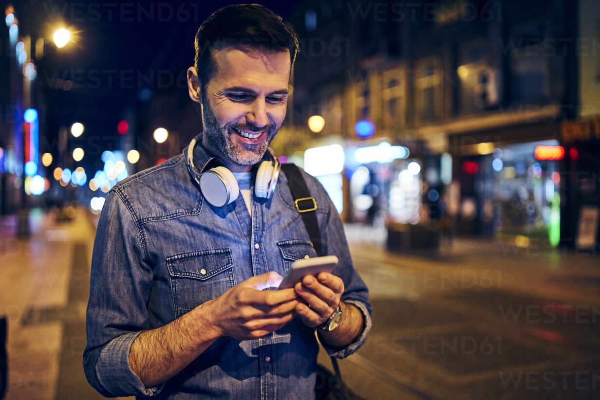 Smiling man using his smartphone in the city at night while waiting for the tram - BSZF01108 - Bartek Szewczyk/Westend61