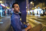 Serious man with wireless headphones waiting for night bus in the city - BSZF01111