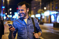 Man with wireless headphones using smartphone in the city at night - BSZF01114