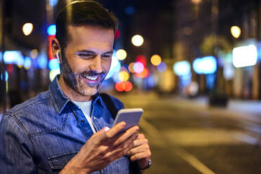 Smiling man with wireless headphones using smartphone in the city at night - BSZF01117