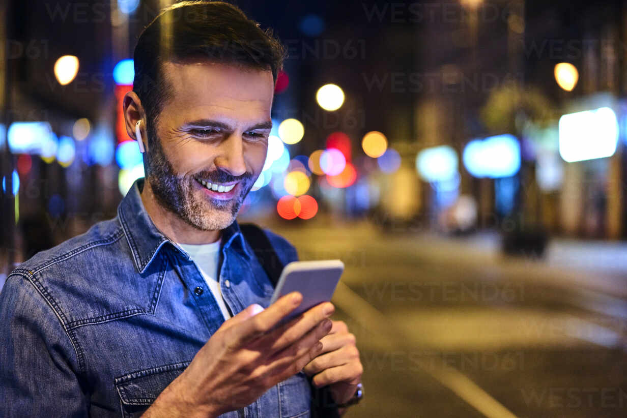 Smiling man with wireless headphones using smartphone in the city at night - BSZF01117 - Bartek Szewczyk/Westend61