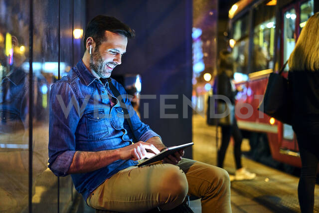 Man with headphones sitting at a station at night using his digital tablet - BSZF01120 - Bartek Szewczyk/Westend61