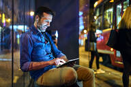 Man with headphones sitting at a station at night using his digital tablet - BSZF01120