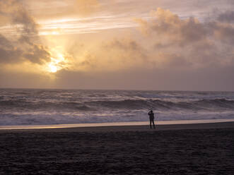 Iceland, Silhouette of person at Reynisfjara Beach - TAMF01760