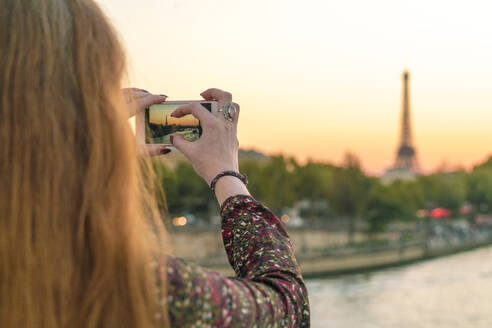 France, Paris, blond woman 30-40 taking photo with mobile from eifel tower - TAMF01766