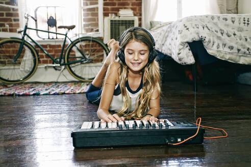 Native American girl playing keyboard in bedroom - BLEF09529