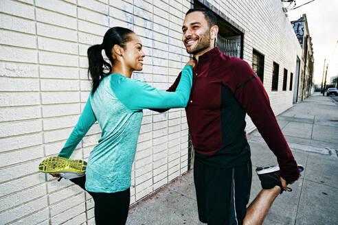 Athletic couple stretching on sidewalk - BLEF09568