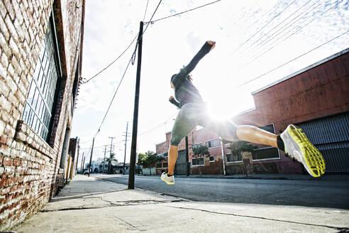 Mixed race athlete jogging on sidewalk - BLEF09571