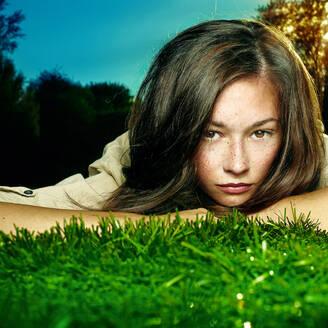 Caucasian teenage girl laying in grass - BLEF09658