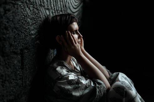 Russia, Moscow, Tired woman with eyes closed and head in hands sitting by wall - OGF00035