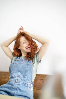 Cheerful redhead woman sitting with arms raised against white wall at home - DMOF00154