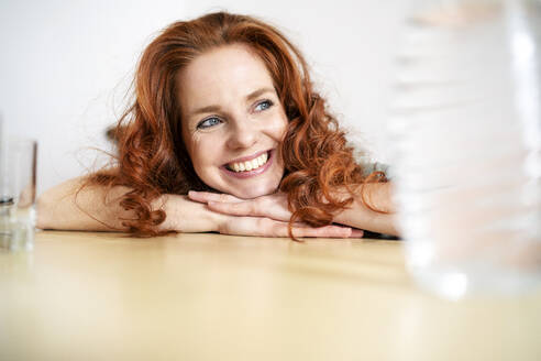 Thoughtful redhead woman leaning on table while looking away at home - DMOF00157